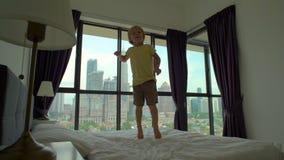 Slowmotion schot van een kleine jongen die op een bed springen Matras en hoofdkussenconcept stock video