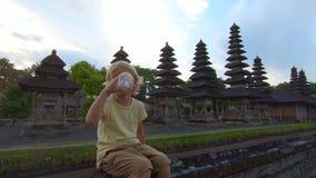 Slowmotion schot van een kleine jongen die water van een plastic flessenzitting op een muur van de tempel van Taman Ayun drinkt stock videobeelden