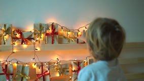 Slowmotion schot van een kleine jongen neemt een heden van een komstkalender die op een bed hangen dat met wordt verlicht stock videobeelden