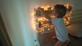 Slowmotion schot van een kleine jongen neemt een heden van een komstkalender die op een bed hangen dat met wordt verlicht stock video