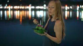 Slowmotion schot van een mooie jonge vrouw die een kaars houdend een krathong in haar handen vierend een Loi aansteekt stock videobeelden