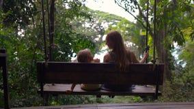 Slowmotion schot van jonge vrouw en haar zoon die op een schommeling in een tropische tuin slingeren stock videobeelden
