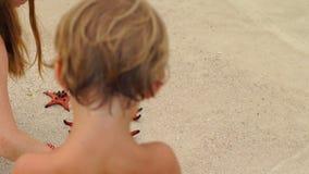 Slowmotion schot - vrouw en haar zoon op een strand met rode zeesterren stock footage