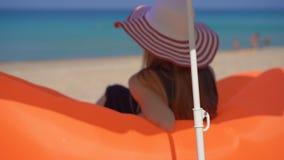 Slowmotion Schuss einer jungen Frau auf einem tropischen Strand, der auf einem aufblasbaren Sofa sitzt Reisenkoffer mit Meerblick stock video footage