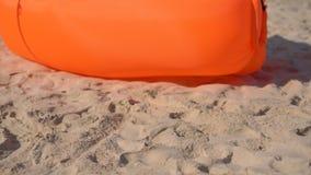 Slowmotion Schuss einer jungen Frau auf einem tropischen Strand, der auf einem aufblasbaren Sofa sitzt Reisenkoffer mit Meerblick stock video