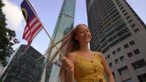 Slowmotion Schuss einer jungen Frau, die malaysische Flagge mit Wolkenkratzern an einem Hintergrund wellenartig bewegt Reise zu M stock video footage