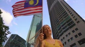 Slowmotion Schuss einer jungen Frau, die malaysische Flagge mit Wolkenkratzern an einem Hintergrund wellenartig bewegt Reise zu M stock footage