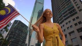 Slowmotion Schuss einer jungen Frau, die malaysische Flagge mit Wolkenkratzern an einem Hintergrund wellenartig bewegt Reise zu M stock video