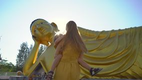 Slowmotion Schuss einer jungen Frau und ihres kleinen Sohns, die Spa? vor einer Statue des L?genbuddhas auf Phuket-Insel haben stock footage