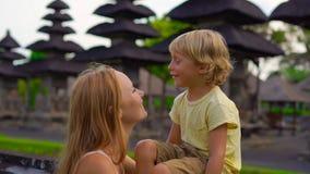 Slowmotion Schuss einer jungen Frau und ihres Sohns, die um den Tempel Taman Ayun auf der Bali-Insel gehen stock video