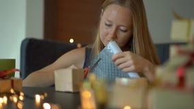 Slowmotion Schuss einer jungen Frau verpackt Geschenke Geschenk eingewickelt im Kraftpapier mit einem Rot- und Goldband f?r stock footage