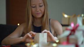 Slowmotion Schuss einer jungen Frau verpackt Geschenke Geschenk eingewickelt im Kraftpapier mit einem Rot- und Goldband f?r stock video footage