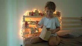 Slowmotion Schuss eines kleinen Jungen, der ein Geschenk von einem Einführungskalender öffnet, der an einem Bett hängt, das erlei stock video footage