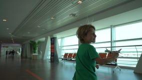 Slowmotion Schuss eines kleinen Jungen der Lauf durch den Flughafen, der weißes Spielzeugflugzeug in seiner Hand hält Getrennt au stock footage