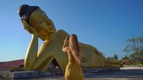 Slowmotion Schuss eines Reisenden der jungen Frau, der an den Wat Srisoonthorn-Tempel mit einer Statue des Lügenbuddhas besucht stock footage