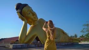 Slowmotion Schuss eines Reisenden der jungen Frau, der an den Wat Srisoonthorn-Tempel mit einer Statue des L?genbuddhas besucht stock video