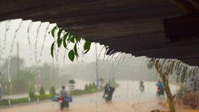 Slowmotion Schuss eines starken Regens und des Wassers, die von einem Dach eines Gebäudes faling sind stock video footage