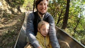Slowmotion Schuss eines Vater- und Sohnreitens hinunter die alpine Achterbahn in einem Herbstwald stock footage