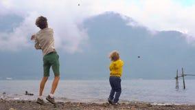 Slowmotion Schuss von werfenden Steinen eines Vaters und des Sohns in den Bratan See in den Hochländern der Bali-Insel, Indonesie stock video footage