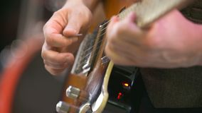 Guitarist playing electrical guitar. Slowmotion shoot of Man guitarist playing electrical guitar on rock music event stock footage