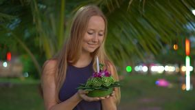 Slowmotion shot of a beautiful young woman holding a krathong in her hands celebrating a Loi Krathong holiday in. Thailand stock video footage