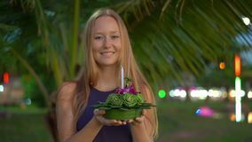 Slowmotion shot of a beautiful young woman holding a krathong in her hands celebrating a Loi Krathong holiday in. Thailand stock video