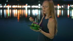Slowmotion shot of a beautiful young woman that lights a candle holding a krathong in her hands celebrating a Loi. Krathong holiday in Thailand stock video footage
