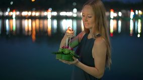 Slowmotion shot of a beautiful young woman that lights a candle holding a krathong in her hands celebrating a Loi. Krathong holiday in Thailand stock footage