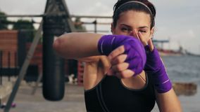 Slowmotion shot: Closeup view of a young woman shadow boxing with her hands wrapped in boxing tapes looking in the stock video