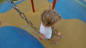 Slowmotion shot of a father swinging his son on swings. Childhood concept stock video
