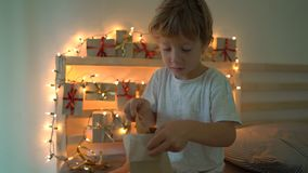 Slowmotion shot of a little boy opening a present from an advent calendar which is hanging on a bed that is lightened. With Christmas lights. Getting ready for stock footage