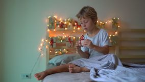 Slowmotion shot of a little boy opening a present from an advent calendar which is hanging on a bed that is lightened. With Christmas lights. Getting ready for stock video footage