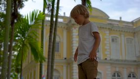 Slowmotion shot of a Little boy playing in front of the City Hall in Georgiatown on Penang island.  stock footage