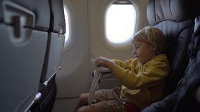 Slowmotion shot of a little boy that plays with white toy airplane sitting in a chair onboard of an airplane. Freedom. Concept. Childhood concept. Children stock video footage