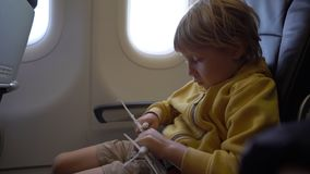 Slowmotion shot of a little boy that plays with white toy airplane sitting in a chair onboard of an airplane. Freedom. Concept. Childhood concept. Children stock footage