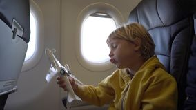 Slowmotion shot of a little boy that plays with white toy airplane sitting in a chair onboard of an airplane. Freedom. Concept. Childhood concept. Children stock video