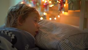 Slowmotion shot of a little boy sleeping in his bed with an advent calendar lighten with Christmas lights shines on a. Back of his bed. Getting ready for stock footage