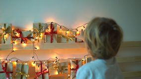Slowmotion shot of a little boy takes a present from an advent calendar hanging on a bed that is lightened with. Christmas lights. Getting ready for Christmas stock video footage