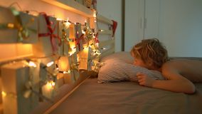 Slowmotion shot of a little boy wakes up and sees an advent calendar hanging on a bed lighten with Christmas lights. Getting ready for Christmas and New Year stock footage