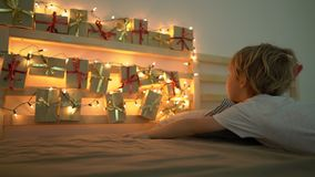 Slowmotion shot of a little boy wakes up and sees an advent calendar hanging on a bed lighten with Christmas lights. Getting ready for Christmas and New Year stock video footage