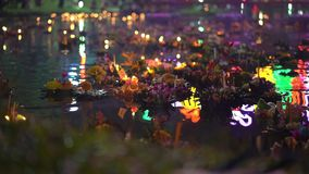 Slowmotion shot of lots of krathongs floating on the water. Celebrating a traditional Thai holiday - Loy Krathong.  stock footage