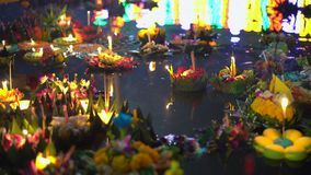 Slowmotion shot of lots of krathongs floating on the water. Celebrating a traditional Thai holiday - Loy Krathong.  stock video