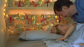 Slowmotion shot offather waking up his little son. He wakes up the boy and shows him an advent calendar that he had made. By himself. Getting ready for stock footage