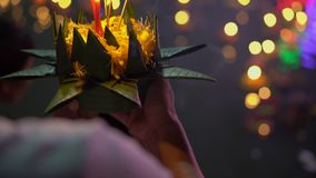 Slowmotion shot of a person holding a krathong with a burning candle in his hands. Celebrating a traditional Thai. Holiday - Loy Krathong stock video