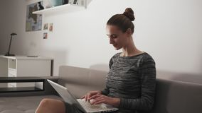 Slowmotion shot: Smiling woman working at home: she is sitting on the sofa, working with a laptop and typing text. Looking at the screen stock video footage