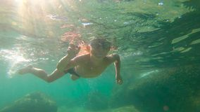 Slowmotion shot of a toddler boy snorkeling in a sea. Slowmotion shot of a toddler boy snorkeling in a sea stock video