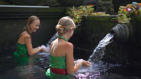 Slowmotion shot of two young women visiting the holly springs in Indonesia. Tirta Empul holy water springs on the Bali