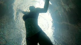 Slowmotion shot view from a bottom of a pool - wooman swims over the camera.  stock video