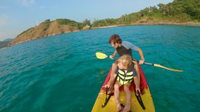 Slowmotion shot of a young family kayaking in a tropical sea and having fun looking at coral reef and tropical fishes stock video