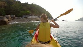 Slowmotion shot of a young family kayaking in a tropical sea and having fun looking at coral reef and tropical fishes stock video footage
